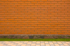 Brick wall with a stone border. And green grass Stock Photography