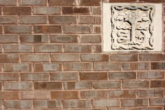 Brick Wall With Stone Carving. A brick wall with an inset stone carving Royalty Free Stock Photography