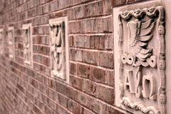 Brick Wall With Stone Carvings. A brick wall with a series of stone carvings shot with a shallow depth of field Stock Photography