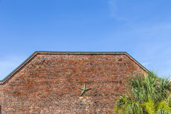 Brick wall texture with metal star. Background of brick wall texture with construction to keep stability under blue sky Stock Images