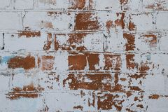 Brick wall texture in old white paint closeup. Wall of red brick painted white peeling paint. Space texture. Old grunge wall backg stock photography
