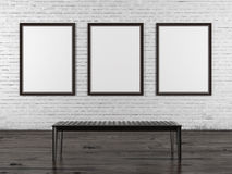 Brick wall with three empty frames and bench. Interior with three empty frames and black bench Stock Photos