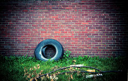 Brick Wall and Tire. A grungy background image of a brick wall and abandoned tire Royalty Free Stock Image