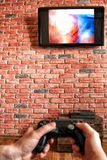Brick wall with a TV and a remote control from the game console in hand. Focus on the wall with TV stock image