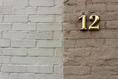 Brick wall in two colors of tan and brown with a gold  12 on the face of it Stock Photography