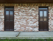 Brick wall with two doors, wooden terrace and grass Stock Photography