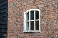 Brick wall with white painted concrete window. In a restored Dutch farmhouse. The white paint has partly been peeled off. The rest of the wall consists of black royalty free stock photography