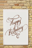 Brick wall and white sheet and text Happy Birthday. Calligraphy lettering Royalty Free Stock Photos