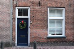 Brick wall with window and door with christmas wreath stock photo