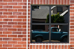 Brick wall with window and reflection of truck Stock Photos