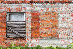 Brick wall and windows. Old red brick wall with some windows and green grass, architecture background Royalty Free Stock Photography