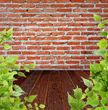 Brick wall and wooden floor with leaves Stock Image