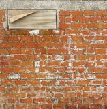 Brick wall with wooden peeling panel Royalty Free Stock Photo