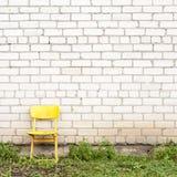 Brick wall and yellow seat Royalty Free Stock Image