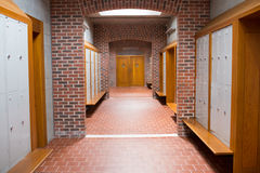 Brick walled corridor with tiled flooring in college Stock Images