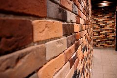 The passage in the wall, a tunnel of colored bricks in brown and beige tones stock photography