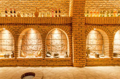 Brick walls of old wine cellar Khareba Winery with many bottles in underground cool room Royalty Free Stock Images