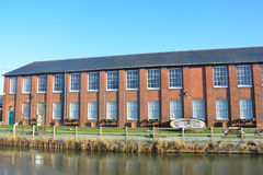 Brick warehouse by river Stock Image