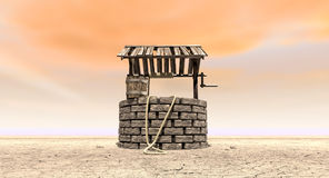 Wishing Well With Wooden Bucket On A Barren Landscape. A brick water well with a wooden roof and bucket attached to a rope in a flat barren landscape with an Stock Photo