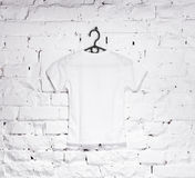 Brick whitewashed wall with white t-shirt on hanger Royalty Free Stock Images