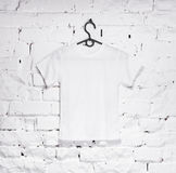 Brick whitewashed wall with white t-shirt on hanger Stock Photos