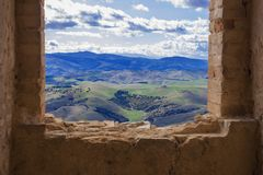 View from a ruined window on green fields royalty free stock image
