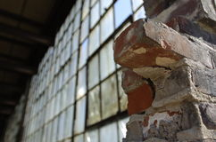 Brick and window wall. Old brick wall partially gone exposing old glass window wall behind.  low angle shot Stock Photography