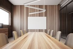 Brick and wood conference room interior poster. Brick meeting room interior with a glass wall and a long table with beige chairs. Ceiling lamps and a poster. A Stock Photo