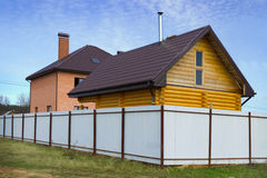 Brick and wooden house behind a fence Stock Photos