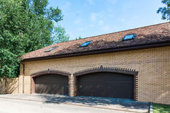 Brick yellow garage. In a private house with a brown gate closed royalty free stock photo