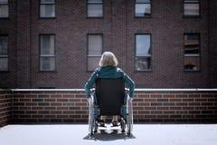 bricked大厦围拢的轮椅的孤独的妇女 免版税库存图片