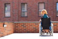 bricked大厦围拢的轮椅的愉快的妇女 库存图片