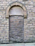 Bricked övre och svärtad dörröppning i en gammal stenbyggnad royaltyfria bilder