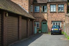 Bricked house with garages. Car parked in front of a bricked house with garages royalty free stock images