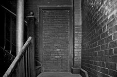 Bricked up. Doorway in dark stairwell in building from the 1800s Stock Images