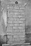 Bricked up door. And weathered wall of an abandoned building. Black and white royalty free stock photo