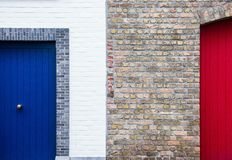 Bricked Wall in Between of Red and Blue Painted Door during Daytime Stock Photo