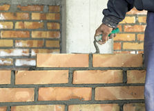 Bricklayer. The worker laying the brick on the wall in construction Stock Image