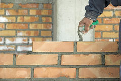 Bricklayer. The worker laying the brick on the wall in construction Royalty Free Stock Photography