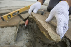 Bricklayer. 's hands in action with the level Royalty Free Stock Photos