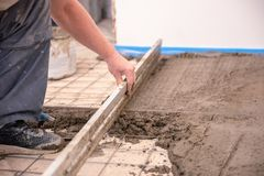 Bricklayer aligns cement screed in a newly built house royalty free stock photo