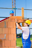 Bricklayer or builders on construction site working Stock Images