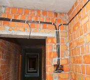 Bricklayer building new house with brick walls, interior rooms,wiring.  Royalty Free Stock Images