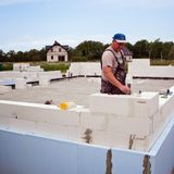 Bricklayer building wall from aerated concrete blocks stock photo