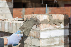 Bricklayer building wall. Using trowel Stock Image