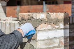 Bricklayer building wall. Using trowel and cement Royalty Free Stock Photography