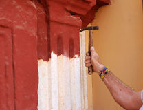 Bricklayer cleaning the stone facade of a Baroque church with pickax Royalty Free Stock Photo