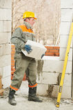 Bricklayer at construction masonry works. Construction mason worker bricklayer lifting and installing calcium silicate brick Royalty Free Stock Image