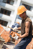 Bricklayer cutting brick with masonry hammer Stock Photos