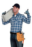 Bricklayer holding concrete block Royalty Free Stock Photography